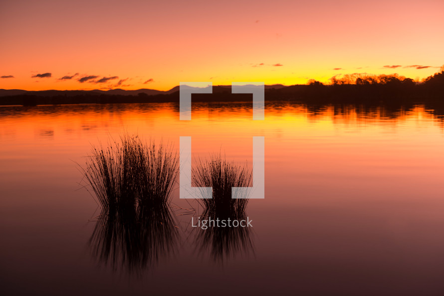 A calm lake lit by the sunset.