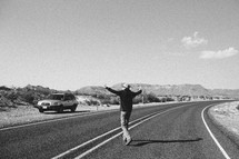 man with open arms standing in the middle of a road