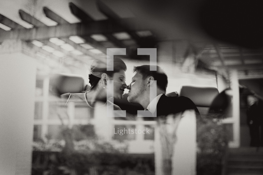 reflection of a bride and groom kissing