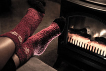 Feet in Red Woolen Christmas Socks by Fireplace