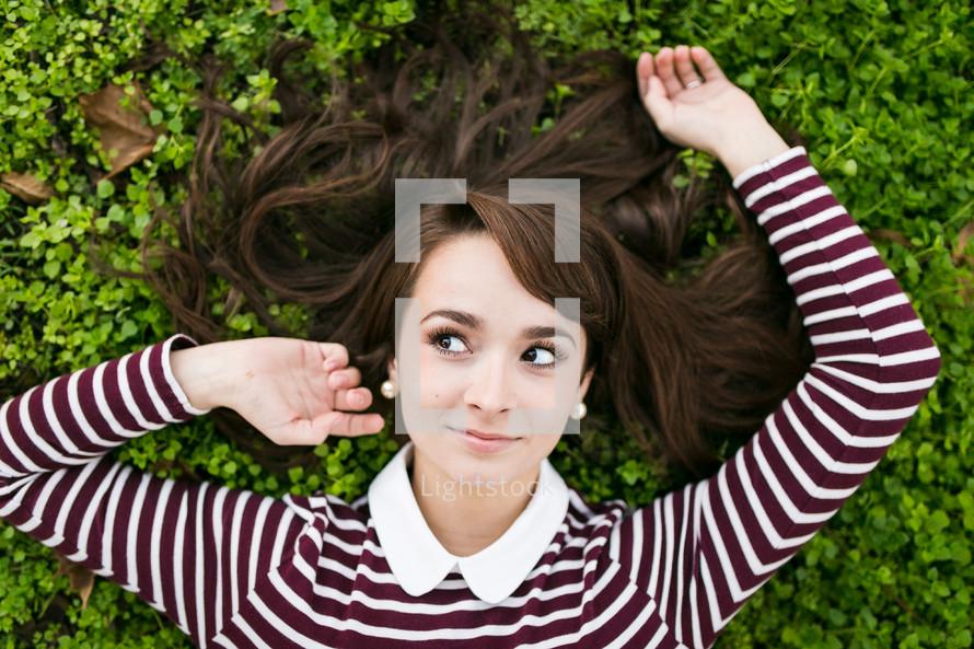 a teen girl lying in green grass