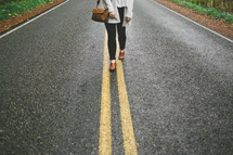 a woman walking down the middle of a road