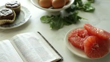open Bible on a table with breakfast