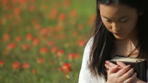 a woman holding a Bible against her chest praying in a meadow of flowers