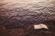 Bible open at the edge of a waterway