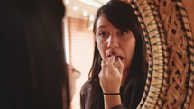 a woman putting on makeup in a mirror
