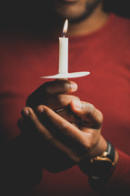 a man holding a candle at a Christmas Eve service