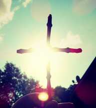cross made of sticks in sunlight