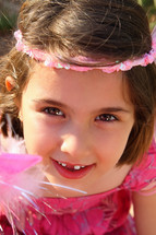 little girl with missing teeth dressed like a princess