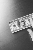 Hand touching $100 bill.