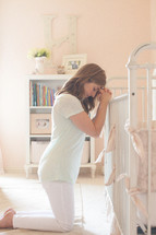 Woman kneeling by crib, praying over infant.