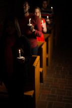parishioners standing holding candles at a Christmas Eve service