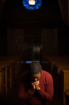 a man kneeling in a church aisle praying
