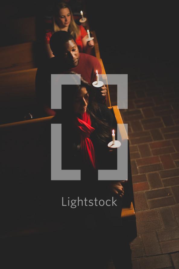 parishioners, congregation, worship service, sitting, church, pews, holding, candles, Christmas Eve, candlelight service, worship