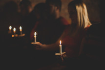parishioners holding candles at a Christmas Eve worship service