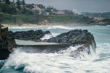 Waves crashing upon a rocky shore near a beach community.