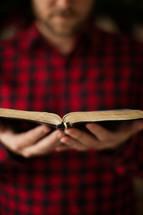 man, plaid shirt, reading, Bible, open Bible