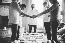 Men and women holding hands in a prayer circle during a Bible study.