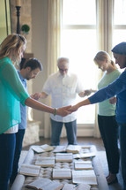 group holding hands in prayer at a Bible study