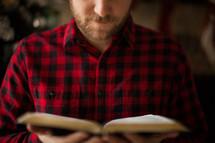 a man in a plaid shirt reading a Bible