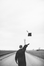 man tossing his graduation cap into the air