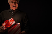 Opening a gift box - An illuminated gift - the gift of salvation through Jesus Christ