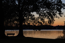 sunset and a park bench by a lake