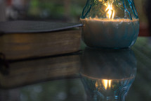 Bible and candle on glass table top