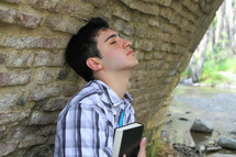 man with head tilted up holding a Bible close to his heart