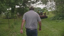 a man walking towards a bailing tractor