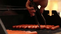 Hand with tongs turning hot dogs on a grill.