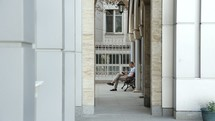 a man sitting on a bench in an alley reading a Bible outdoors
