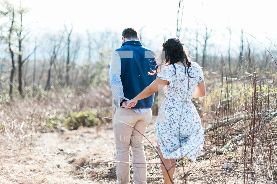 a couple holding hands walking through a field