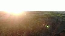 green mountainside and sunburst