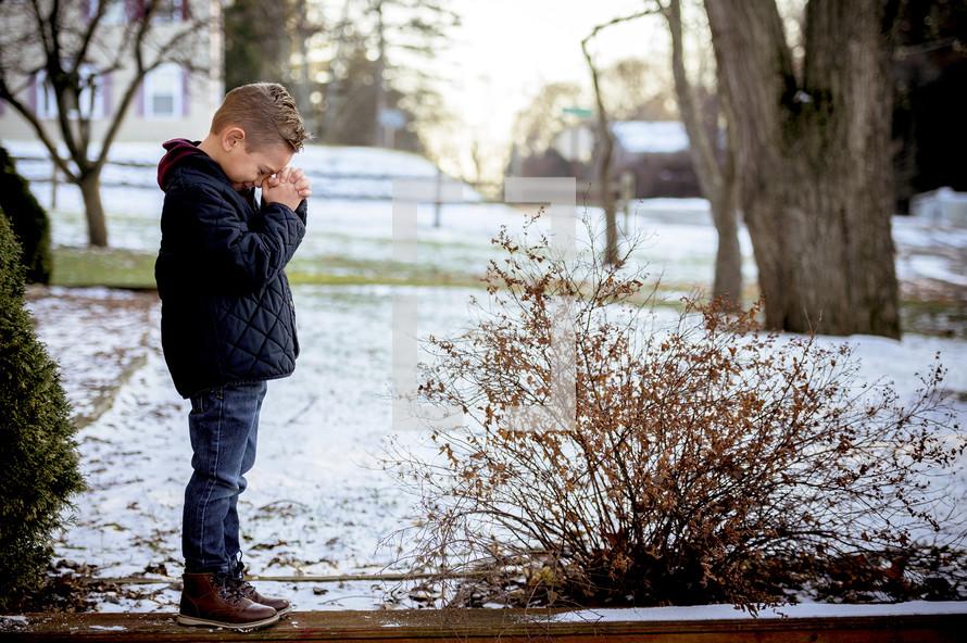 boy child praying outdoors in snow