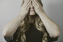 woman covering her face with her hands