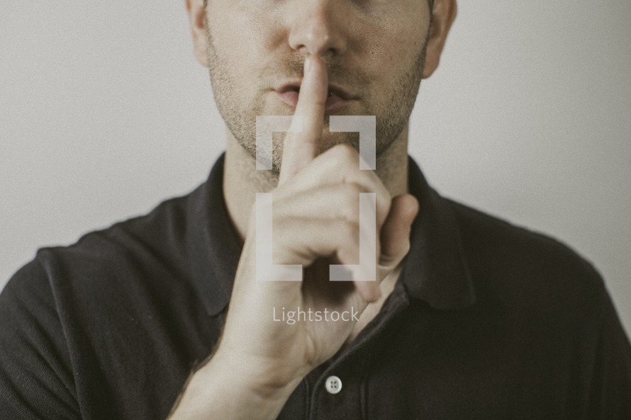 man holding his finger over his mouth