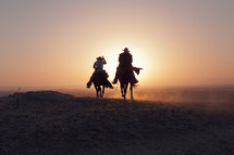 cowboys riding horses at sunset
