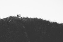 a couple standing on a hilltop