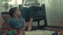 grandmother rocking in a rocking chair while watching a grandbaby