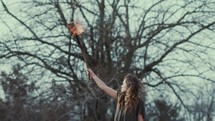a woman holding up a burning torch