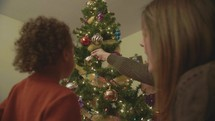 mother and son decorating a Christmas tree