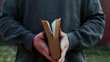 man closing a Bible