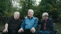 elderly men talking on a park bench