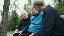 elderly men talking sitting on a park bench