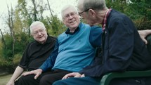 elderly men talking sitting on a park bench