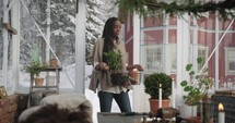a woman walking through the snow to a greenhouse