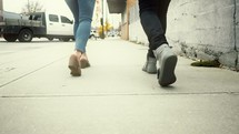 legs of a couple walking on a sidewalk