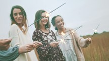 women holding sparklers