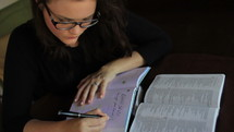 woman journaling and an open Bible